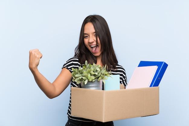 Giovane ragazza bruna che fa una mossa mentre raccoglie una scatola piena di cose per celebrare una vittoria
