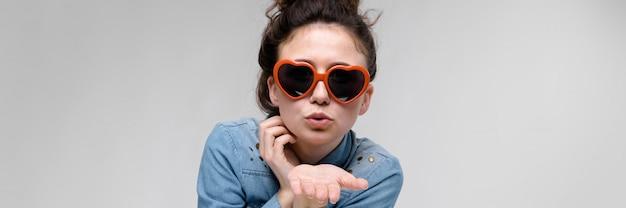 Giovane ragazza bruna con gli occhiali a forma di cuore. i peli sono raccolti in una crocchia. la ragazza manda un bacio aereo.