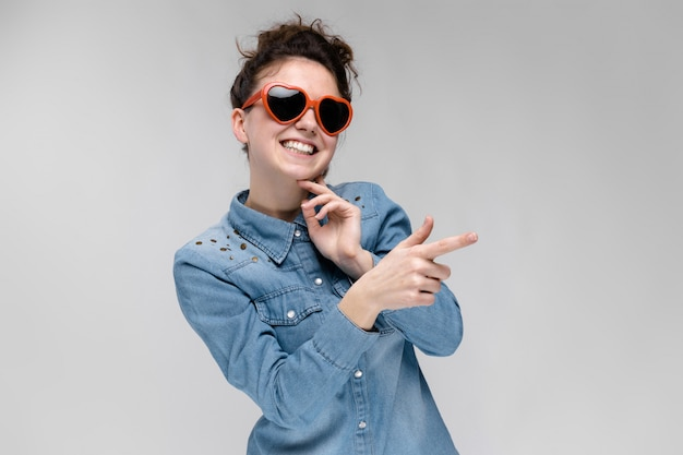 Giovane ragazza bruna con gli occhiali a forma di cuore. i peli sono raccolti in una crocchia. la ragazza sta indicando con il dito.