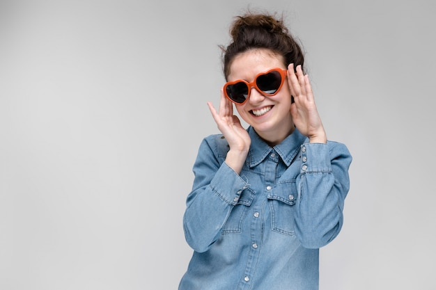 Giovane ragazza bruna con gli occhiali a forma di cuore.