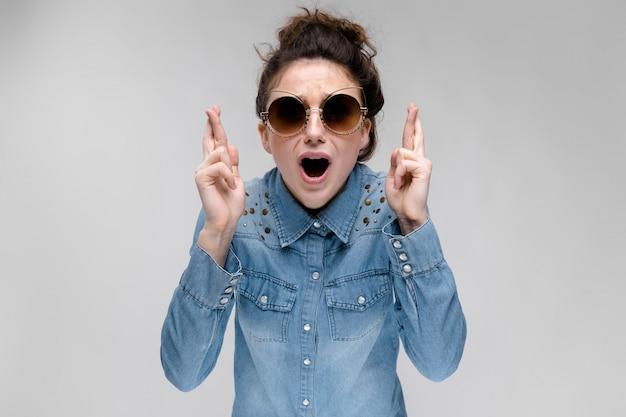 Giovane ragazza bruna con gli occhiali neri. occhiali per gatti. i capelli sono raccolti in una crocchia. la ragazza incrociò le dita.