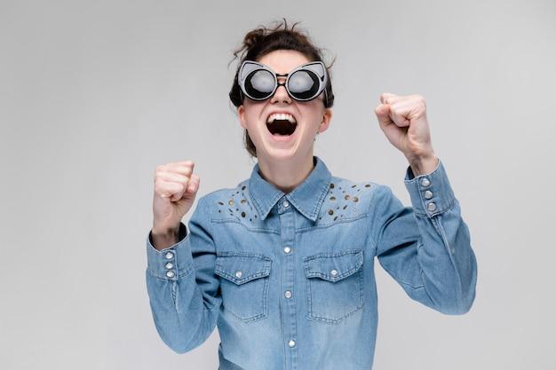 Giovane ragazza bruna con gli occhiali neri. occhiali per gatti. i capelli sono raccolti in una crocchia. la ragazza strinse le mani in pugni.