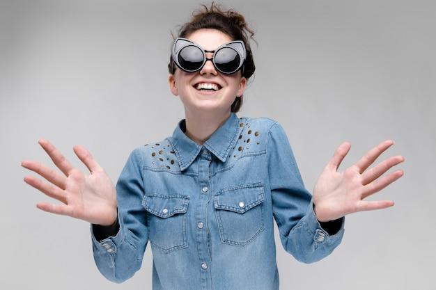 Giovane ragazza bruna con gli occhiali neri. occhiali per gatti. i capelli sono raccolti in una crocchia. la ragazza tira avanti i palmi delle mani.