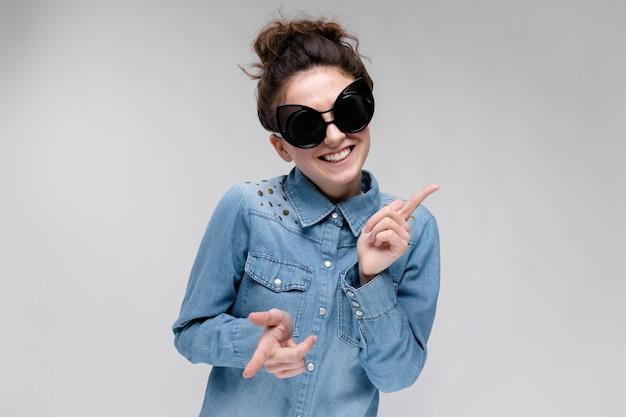 Giovane ragazza bruna con gli occhiali neri. occhiali per gatti. i capelli sono raccolti in una crocchia. ragazza che balla