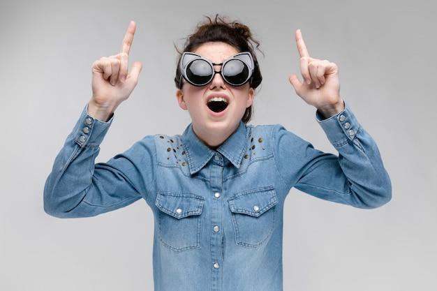 Giovane ragazza bruna con gli occhiali neri. occhiali per gatti. i capelli sono raccolti in una crocchia.