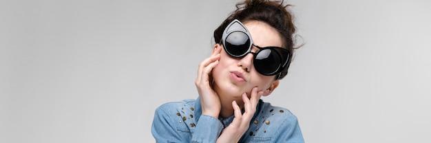 Giovane ragazza bruna con gli occhiali neri