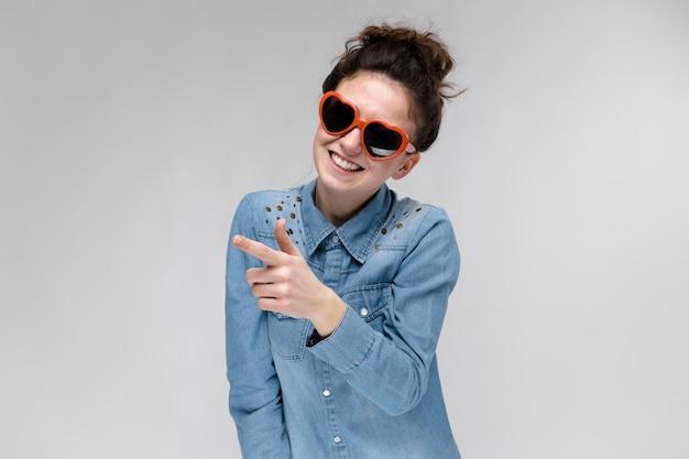 Giovane ragazza bruna con gli occhiali sotto forma di un cuore.