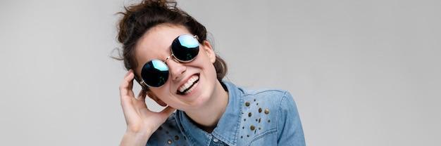Giovane ragazza bruna in occhiali rotondi. i peli sono raccolti in una crocchia. la ragazza si portò una mano alla testa.