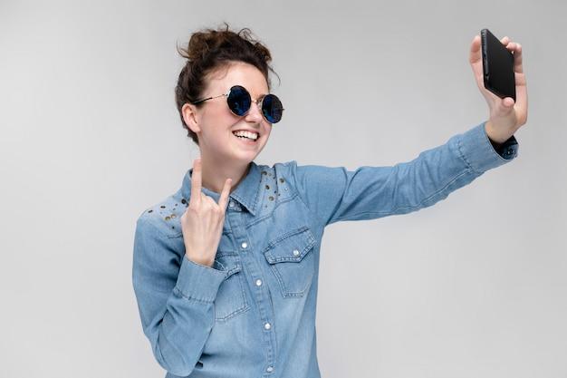 Giovane ragazza bruna in occhiali rotondi. i peli sono raccolti in una crocchia. ragazza con un telefono nero. la ragazza fa selfie.