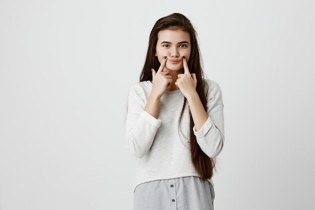 Giovane ragazza bruna sconvolta adolescente facendo un sorriso falso con le dita che allungano gli angoli della bocca. ritratto di donna che cerca di rimanere positivo
