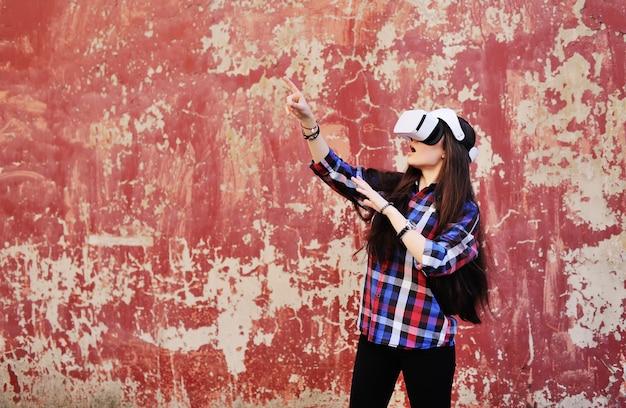 Giovane ragazza carina con i capelli lunghi in camicia a scacchi in bicchieri di realtà virtuale su priorità bassa rossa della parete del grunge.