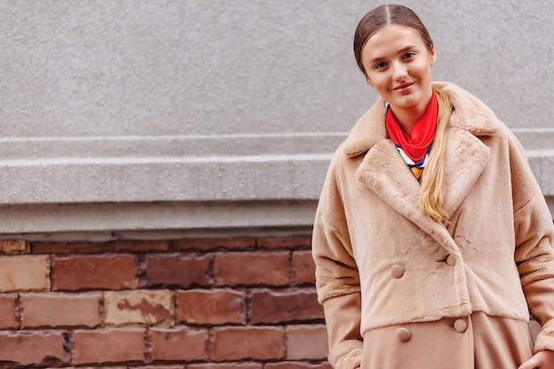Giovane ragazza carina elegante in una pelliccia passeggiando per la città vicino a case in legno e muri in pietra
