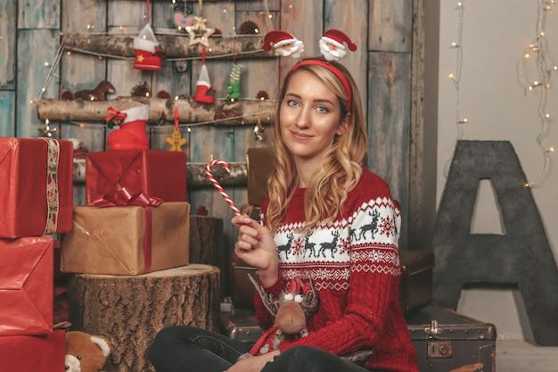Giovane ragazza carina nell'immagine di un nuovo anno tra i regali e le decorazioni natalizie