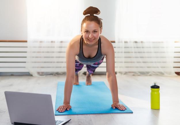 Giovane ragazza carina pratica yoga a casa, prendendo le pose e guardando un computer portatile
