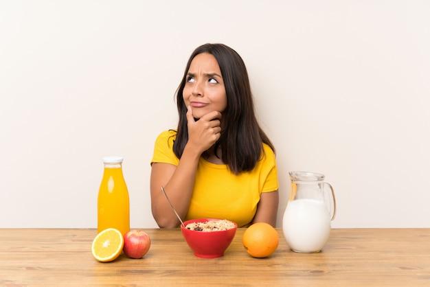 Giovane ragazza castana che mangia il latte della prima colazione che pensa un'idea