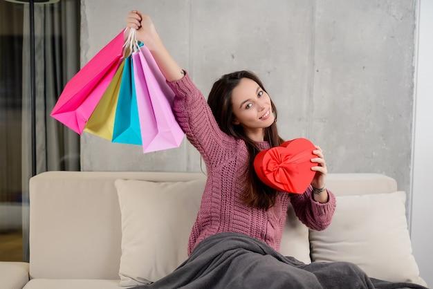 Giovane ragazza castana che tiene i sacchetti della spesa variopinti e una scatola attuale in forma di cuore