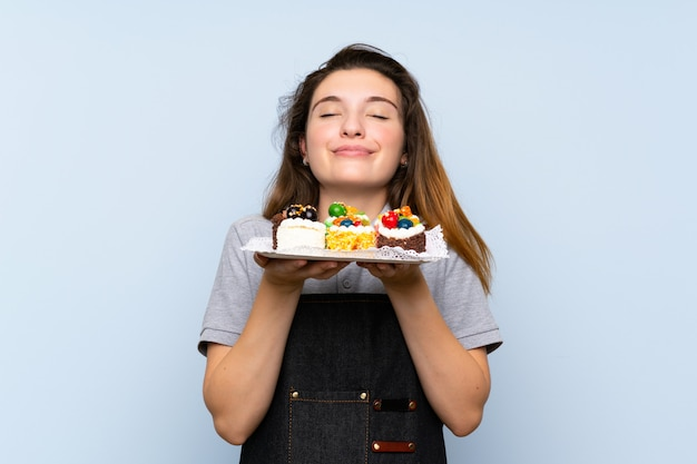Giovane ragazza castana che tiene le mini torte che godono dell'odore di loro