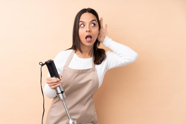 Giovane ragazza castana che usando il miscelatore della mano che ascolta qualcosa mettendo la mano sull'orecchio