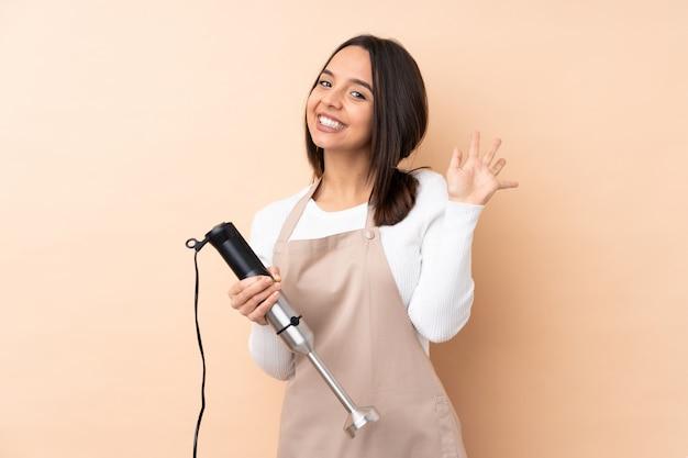 Giovane ragazza castana che usando il miscelatore della mano sopra la parete isolata che saluta con la mano con l'espressione felice