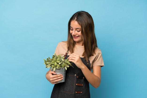 Giovane ragazza castana sopra il blu isolato che prende un vaso da fiori