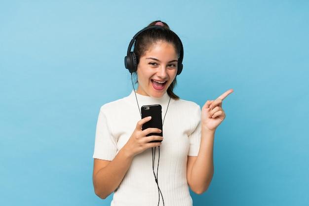 Giovane ragazza castana sopra il blu isolato usando il cellulare con le cuffie e cantando