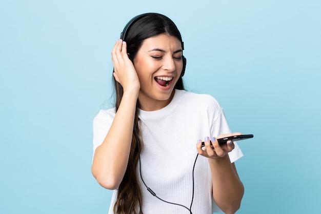 Giovane ragazza castana sopra musica d'ascolto isolata della parete blu con un cellulare e un canto