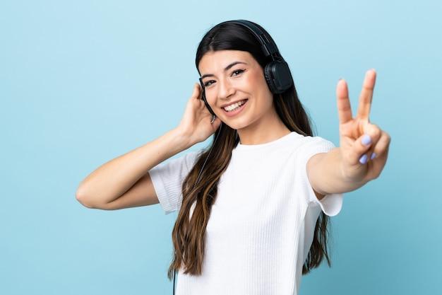 Giovane ragazza castana sopra musica e canto d'ascolto blu isolati