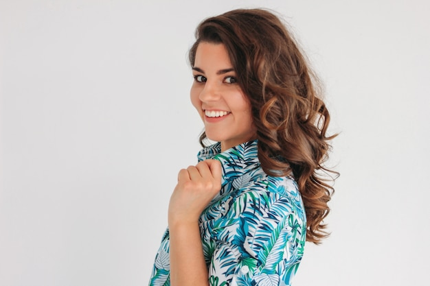 Giovane ragazza castana sorridente affascinante con capelli ondulati in vestito da estate, isolato su bianco