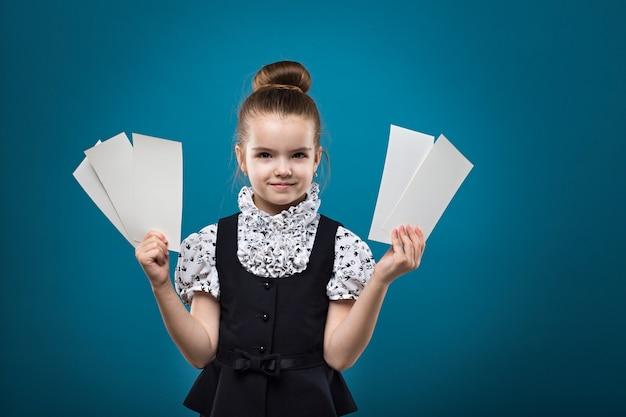 Giovane ragazza caucasica carina mostrando biglietti e sorridente