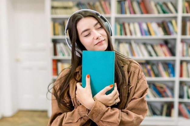 Giovane ragazza caucasica felice dello studente che studia alla biblioteca, ascoltando le cuffie di musica con grande piacere e gli occhi chiusi, tenendo in mano il libro blu