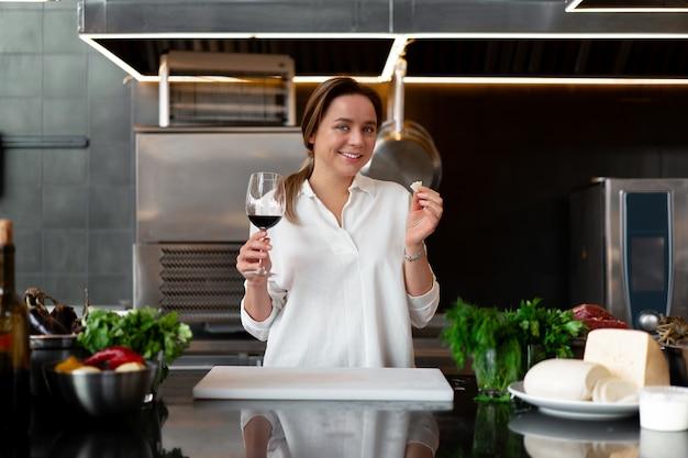 Giovane ragazza caucasica in piedi in cucina in uniforme bianca sorridente e degustazione di vino rosso