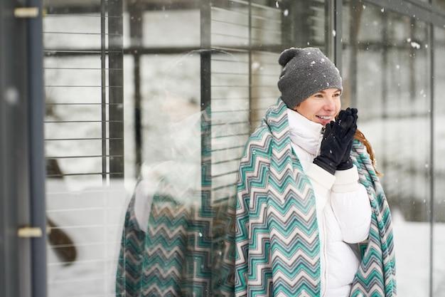 Giovane ragazza caucasica sorridente coperta in mani di riscaldamento del plaid blu dei modelli ghiacciate