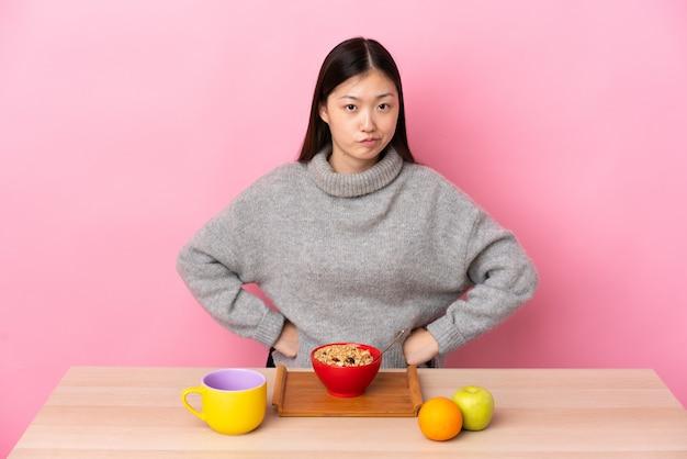 Giovane ragazza cinese che mangia prima colazione in una tabella arrabbiata
