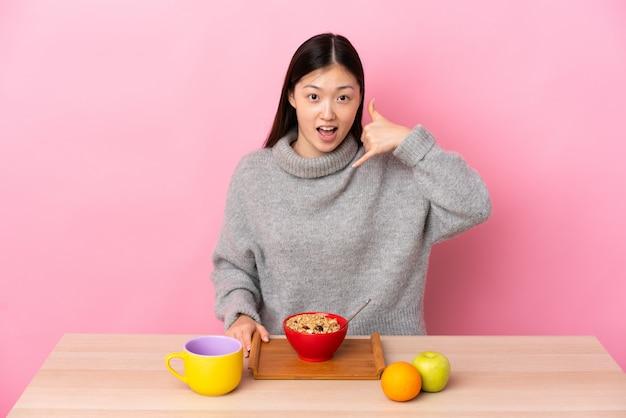 Giovane ragazza cinese che mangia prima colazione in una tabella che fa gesto del telefono. richiamami segno