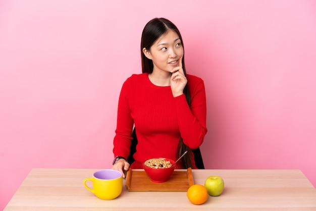 Giovane ragazza cinese che mangia prima colazione in una tavola che pensa un'idea mentre cercando