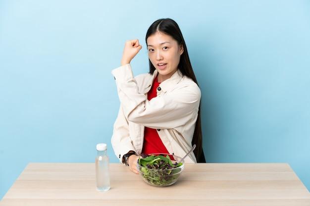 Giovane ragazza cinese che mangia un'insalata che fa forte gesto