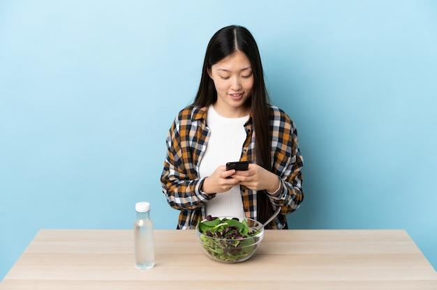 Giovane ragazza cinese che mangia un'insalata che invia un messaggio con il cellulare