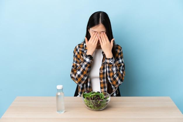 Giovane ragazza cinese che mangia un'insalata con l'espressione stanca e malata