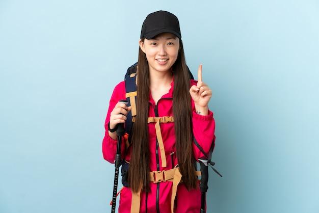 Giovane ragazza cinese con i pali di trekking e dello zaino sopra la parete blu isolata che indica su una grande idea