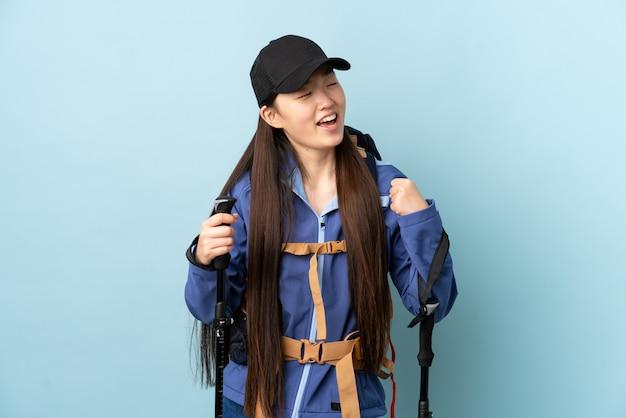 Giovane ragazza cinese con lo zaino e pali di trekking sopra la parete blu isolata che celebra una vittoria
