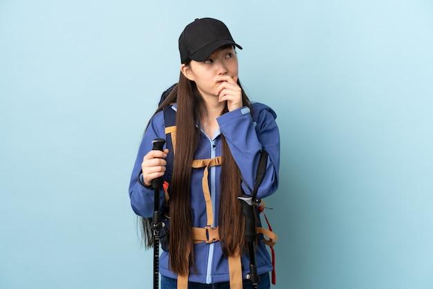 Giovane ragazza cinese con lo zaino e pali di trekking sopra la parete blu isolata che ha dubbi e con l'espressione confusa del fronte