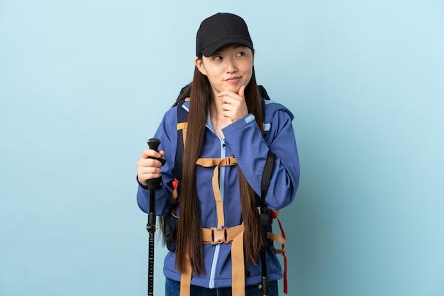 Giovane ragazza cinese con lo zaino e pali di trekking sopra la parete blu isolata che pensa un'idea mentre osservando in su