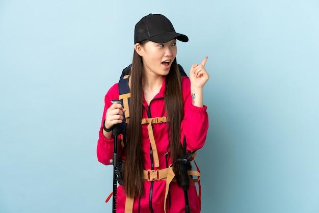 Giovane ragazza cinese con zaino e bastoncini da trekking sul muro blu isolato che intende realizzare la soluzione mentre si solleva un dito