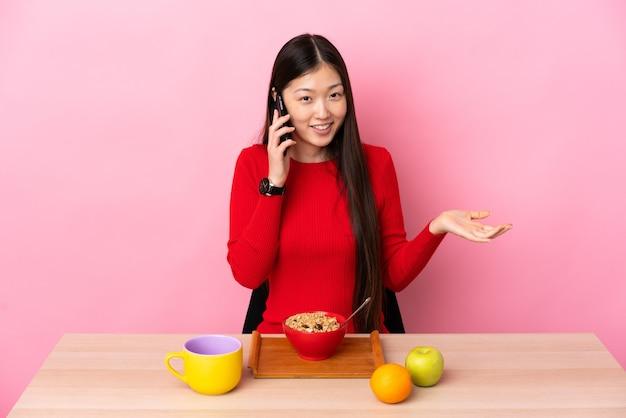 Giovane ragazza cinese facendo colazione in un tavolo mantenendo una conversazione con il telefono cellulare con qualcuno