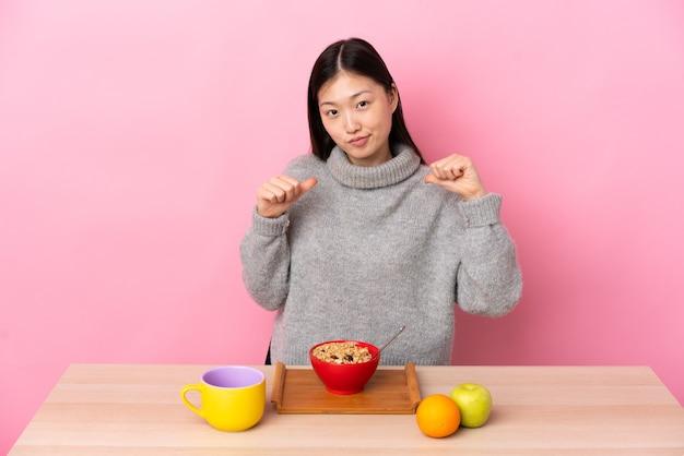Giovane ragazza cinese facendo colazione in un tavolo orgoglioso e soddisfatto di sé