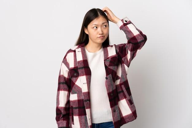 Giovane ragazza cinese sopra la parete bianca isolata che ha dubbi mentre grattandosi la testa