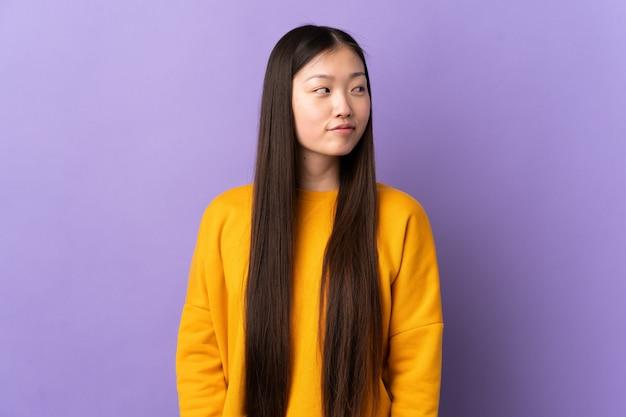 Giovane ragazza cinese sopra la parete viola che ha dubbi mentre sembra laterale