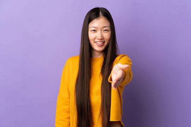 Giovane ragazza cinese sopra la parete viola isolata che stringe le mani per la chiusura molto