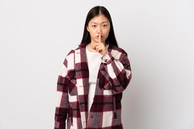 Giovane ragazza cinese sul muro bianco che mostra un segno di silenzio gesto mettendo il dito in bocca