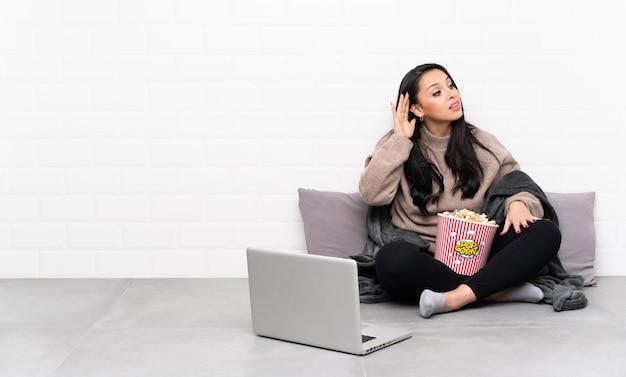 Giovane ragazza colombiana che tiene una ciotola di popcorn e che mostra un film in un computer portatile ascoltando qualcosa mettendo la mano sull'orecchio